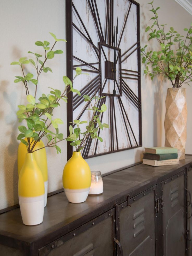 A Large Clock And Colorful Modern Vases Add Contrast While Industrial Cabinets Provide Stylish Storage In The Sitting Room As Seen On HGTVs Fixer Upper