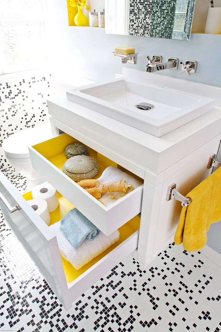 When the drawers in this modern bathroom are closed, the bathroom is primarily black and white with a couple of yellow accents creating an overall look of modern sophistication. But an unexpected pop of color can be seen when opening the drawers that have been painted yellow on the inside.
