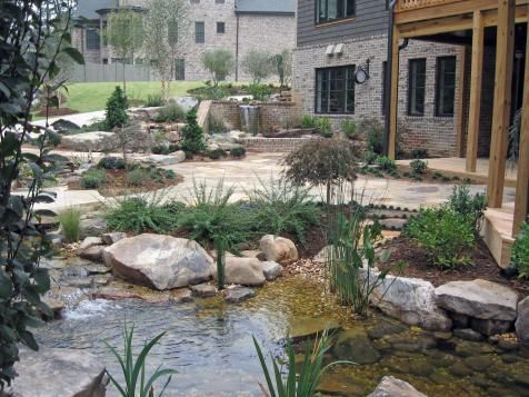 An intricate water feature wraps the entire back end of this dream house; water spills over a brick wall, encircles the patio, flows underneath the breezeway and empties into a fish pond. A raised pond at the head of the feature provides the drop needed for water to flow well and create more waterfall sound. The feature uses a careful mix of large boulders, medium rocks and small pebbles for a natural appearance. Selecting extra-large plant material makes the brand-new house and landscape…