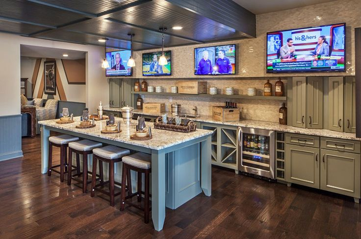 Basement wet bar with bar stools and multiple tvs