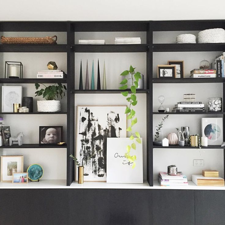 Bookcase styles with art, decor and books. Black full wall bookcase styled with Scandinavian style decor.