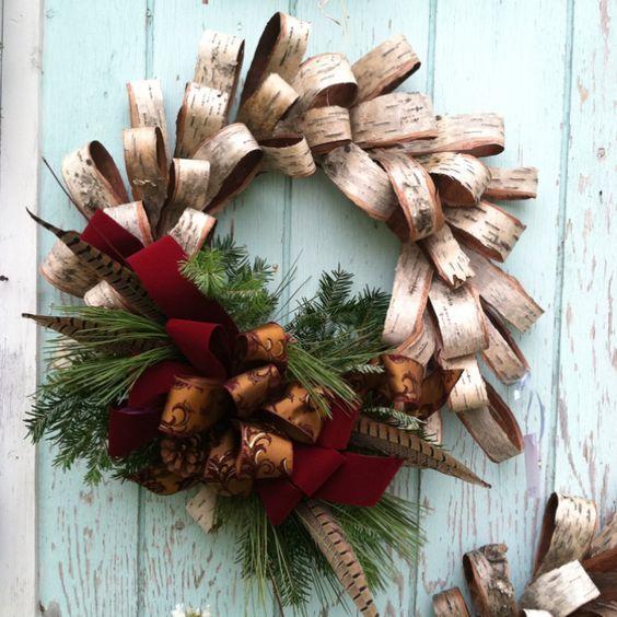Ghirlanda natalizzata realizzata con piccole strisce di corteccia piegate e spillate una sopra l'altra con una decorazione di rametti di abete, pigne e nastro rosso
