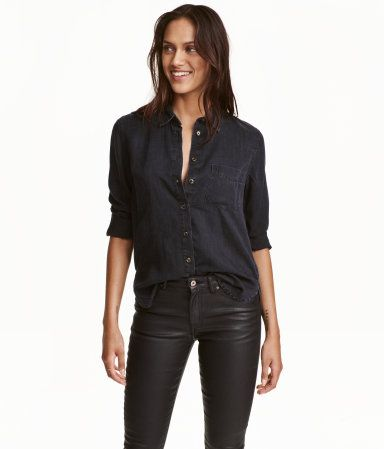 Black. CONSCIOUS. Straight-cut shirt in washed denim made from Tencel® lyocell. Chest pocket, rounded hem with slits at sides, and longer back section.