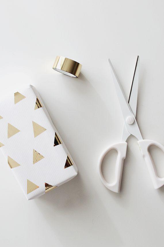 Így készül: 1. Csomagold be fehér papírba az ajándékot. 2. Metálarany dekortapaszból vágj ki háromszögeket. 3. Ragaszd fel a csomagra a háromszögeket.