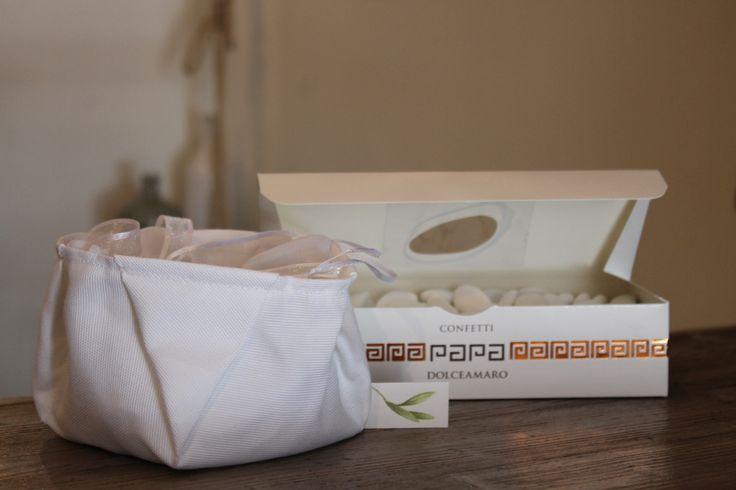 Preparativi per le bomboniere da Oleonauta Borsa in cotone juta, biglietto di Idea d'Arte con foglie d'Ulivo e confetti Papa