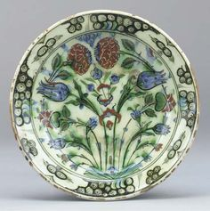 An Ottoman Iznik pottery dish, Turkey, 17th century  Decorated with trailing sprays of tulips and chrysanthemums within a whorl pattern border -- 10¼in. (26cm.) diam.