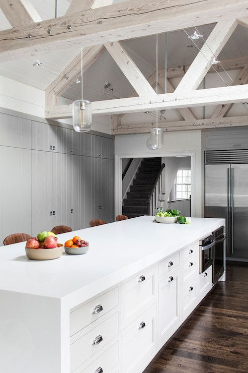 Amazing kitchen with whitewashed truss ceiling beams lit by wire track lighting and a pair of modern glass pendants over a long island fitted with gray cabinets accented with nickel bin pulls as well as microwave and oven. The extra-long island is topped with a thick white waterfall edge counter lined with Cherner Barstools placed in front of with wall to wall gray paneled cabinets filling the back wall.