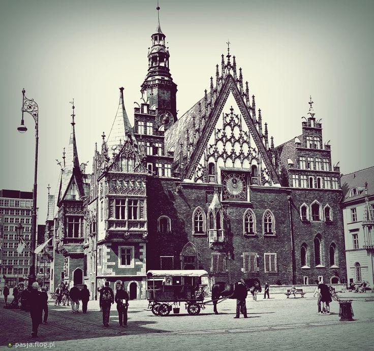 wrocławski ratusz, nieustannie rozbudowywany i remontowany od XIV do XVI wieku; widoczny renesansowy hełm wieży z XIV w (który zastąpił swojego gotyckiego poprzednika); elewacja wschodnia z trzema szczytami zdobionymi sterczynami (pinaklami), z wykuszem i ryzalitem na lewym krańcu; prawy szczyt schodkowy zdobiony prostokątnymi blendami; ratusz choć w charakterze gotycki, nosi na sobie ślady stylu renesansu, północnego manieryzmu oraz baroku.