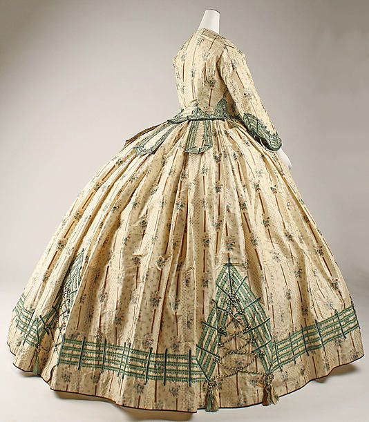 Beautiful hoop skirt dress, 1862. Look at the hem-the corset-like panels and the tassels. Great details!