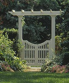 The double-door gate has a scooped top edge and hangs from square posts that support an overhead arbor.