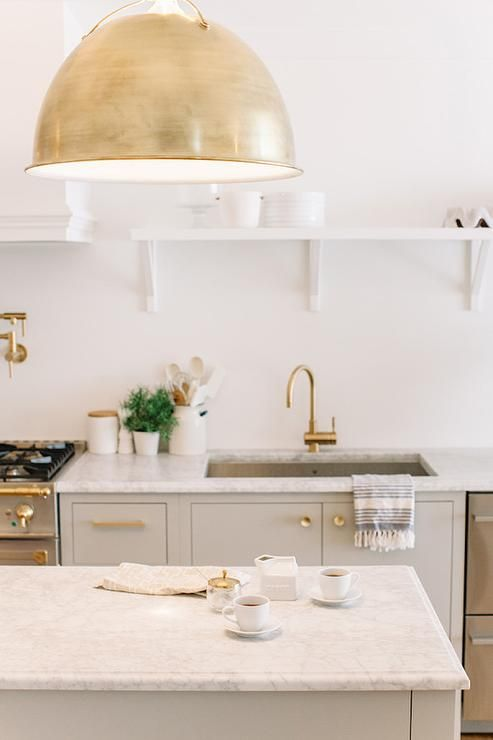 White and gray kitchen features a gray freestanding island topped with white marble illuminated by a Eugene Pendant. Kitchen boasts gray cabinets adorned with brass hardware topped with white marble fitted with a stainless steel sink and brass gooseneck faucet next to stacked dishwasher drawers under a long shelf with corbels.