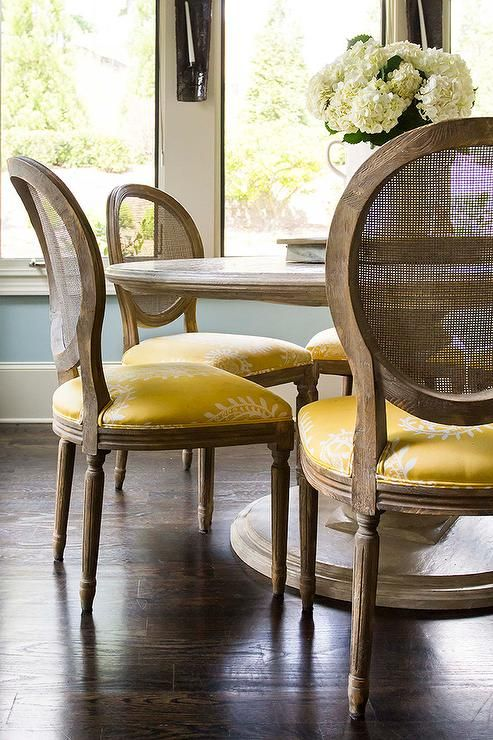 Round Marble Top Dining Table with Round Cane Back Chairs and Yellow Seat Cushions, Transitional, Dining Room