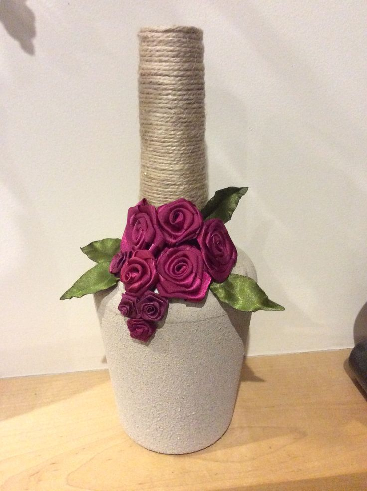 Made from my favourite, a Tia Maria bottle, using textured spray paint, twine and ribbon roses.  Do similar with wine bottles! Or jars!