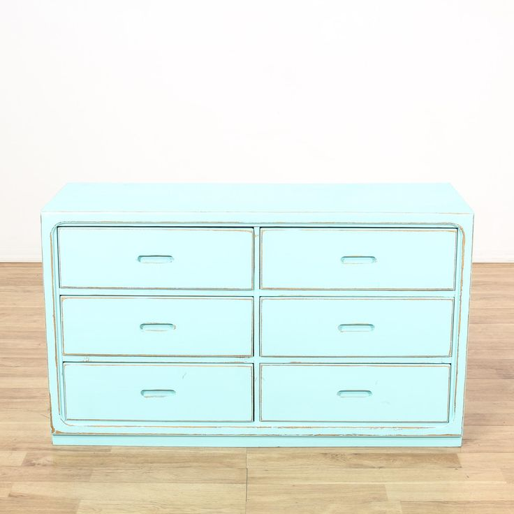 This shabby chic dresser is featured in a solid wood with a distressed light aqua blue paint finish. This short dresser has 6 spacious drawers, carved inset handles and curved edges. Perfect storage piece for adding a pop of color to a room! #shabbychic #dressers #shortdresser #sandiegovintage #vintagefurniture