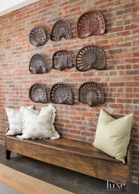 I LOVE the old tractor seats! A Texas country #farmhouse vacation home's #brick #foyer