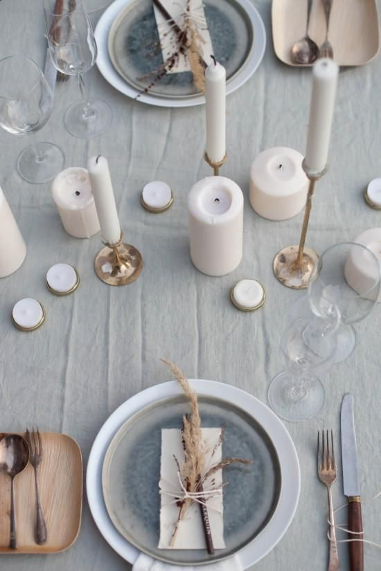 13 Modern Holiday Table Settings That'll Up Your Hosting Game - a mix of pillar candles and brass candlesticks paired with a rustic plate