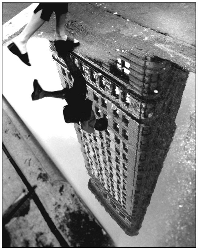 Henri Cartier-Bresson: I like how this is showing a reflection of the building a the person jumping over the puddle.