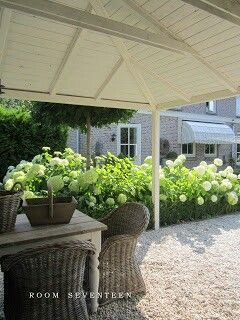 Love the pea gravel, rustic table and wicker chairs
