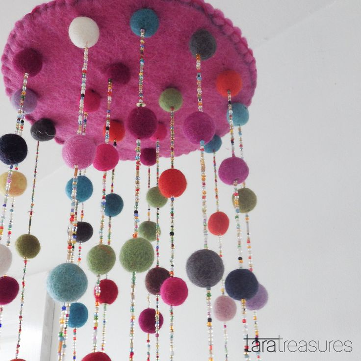 Suspend this colourful mobile over the baby's cot and watch the delight on his or her face. This mobile is made of many felt balls and shiny beads, sewn onto a pink felted wool base. An eye-catching addition to a nursery.