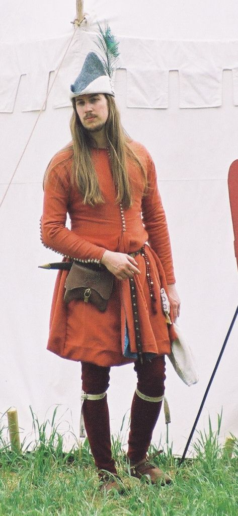 Ritter ca. 1350 in ziviler Kleidung mit krappgefärbter Cotehardie mit Indigogefärbtem Seidenfutter, krappgefärbten Beinlingen, bestickter Gugel, Sporen, golddurchwirkten Kniebändern und Hut