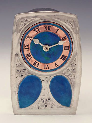 Manufacturer Liberty & Co.  Designer   Description Polished pewter clock from the Liberty 'Tudric' range with enamel & copper dial. The body with two large enamels  Country of Manufacture England  Date c.1905  Marks See photo   Condition Perfect with original movement.   Size 14cms high  Other Information The original clock movement has been fully cleaned and serviced