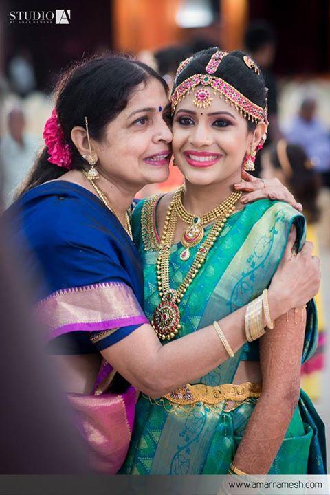 South Indian bride. Gold temple jewelry. Jhumkis.Green teal kanchipuram sari with embroidered pink contrast blouse.Braid with fresh jasmine flowers. Tamil bride. Telugu bride. Kannada bride. Hindu bride. Malayalee bride.Kerala bride.South Indian wedding