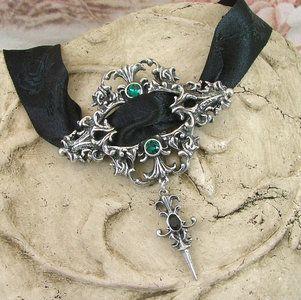 Handgemaakte choker ketting bestaande uit een zwart lint met ingeweven barok rozen en een barok ornament met 2 groene swarovski kristallen. Deze ketting is verstelbaar.  Lengte ketting: 48 tot 52 c...