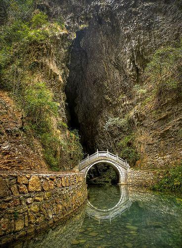 Grotto - moon gate optical illusion w/ the water's reflection in Zhangjiajie, Hunan, China