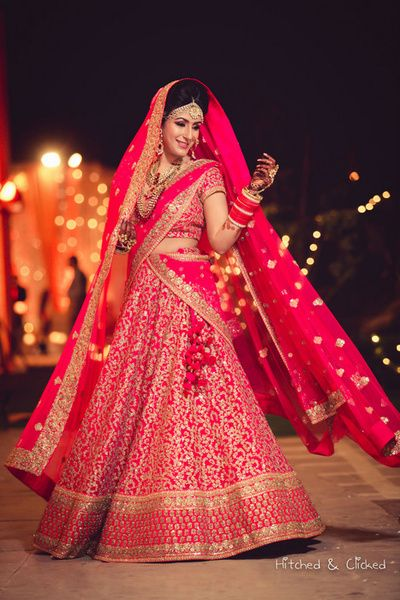 Fuschia pink bridal lehenga by Sabyasachi, pink and gold lehenga , twirling bride, pink bridal lehenga, double dupatta