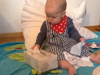 Tissue box filled with squares of material for babies to pull out and then post back