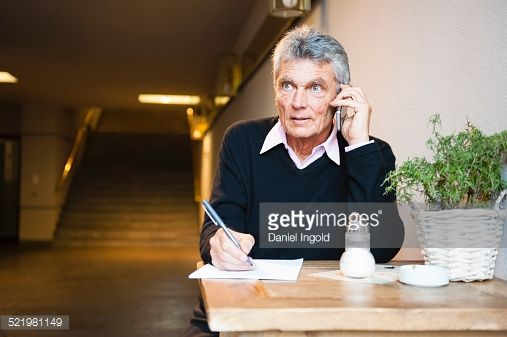 Stock Photo : Senior businessman making notes whilst chatting on smartphone in cafe