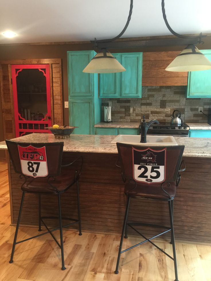 Turquoise Kitchen Cabinets. Western home. Back number chairs.