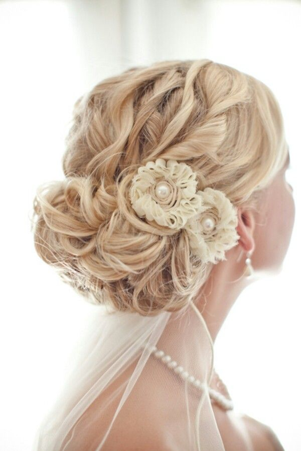 Bridal hair updo with veil and fake flowers.