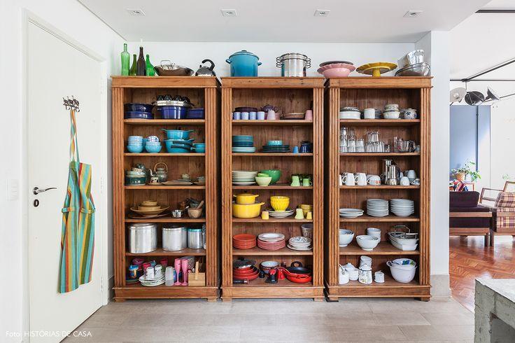 Cozinha tem armários de madeira com louça organizada por cor.