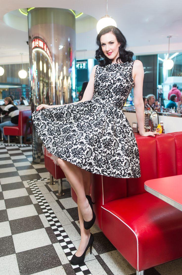 Šaty Lady V London Glamorous Lace Tea Retro šaty ve stylu 50. let z londýnské dílny Lady V London. Jedinečné šaty vhodné pro společenské události - na svatby, maturitní plesy, do tanečních kurzů, lze vynést i jako malé večerní. Nádherné provedení látky připomínající imitaci krajky, černé ornamenty na bílém podkladu s decentním leskem. Příjemný pružný materiál (97%, 3% elastan), pohodlný střih s lodičkových výstřihem, vzadu lehce vykrojené se zapínáním na zip a vázačkou zajistí skvělé…