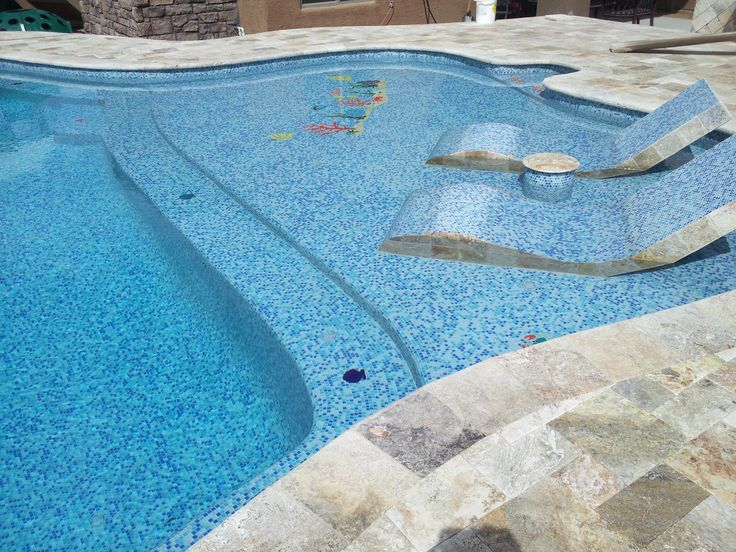 Travertine deck with Pool Jewelz glass tile interior and built in loungers finished in glass tile and travertine.
