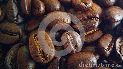 A closeup macro shot of roasted coffee beans on a table.