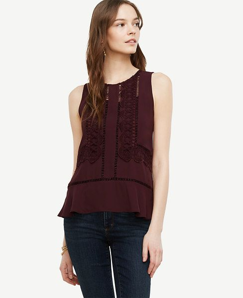 """From the intricate lace to the alluring cutouts, this flouncy piece is endlessly best-dressed. Add a cami beneath for more coverage. Jewel neck. Sleeveless. Back slit with button closure. Flounce hem. 24 1/4"""" long."""