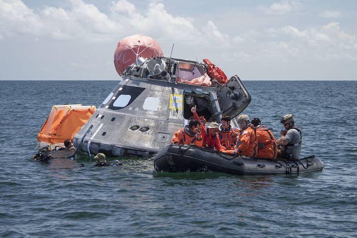 A cápsula de Orion flutua no mar com a tripulação em trajes de vôo laranja na jangada nas proximidades