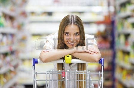 Szczęśliwe blondynka uśmiecha shopper ponad koszyku supermarkecie Zdjęcie Seryjne - 15471540