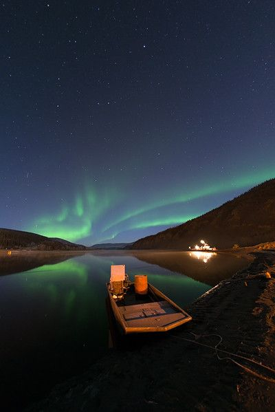 Northern Lights in late fall, Reflection in the Yukon River. The ferry, which is a part of the Highway system, is to see in the back.  Dawson City, Yukon, Canada. By Priska Wettstein