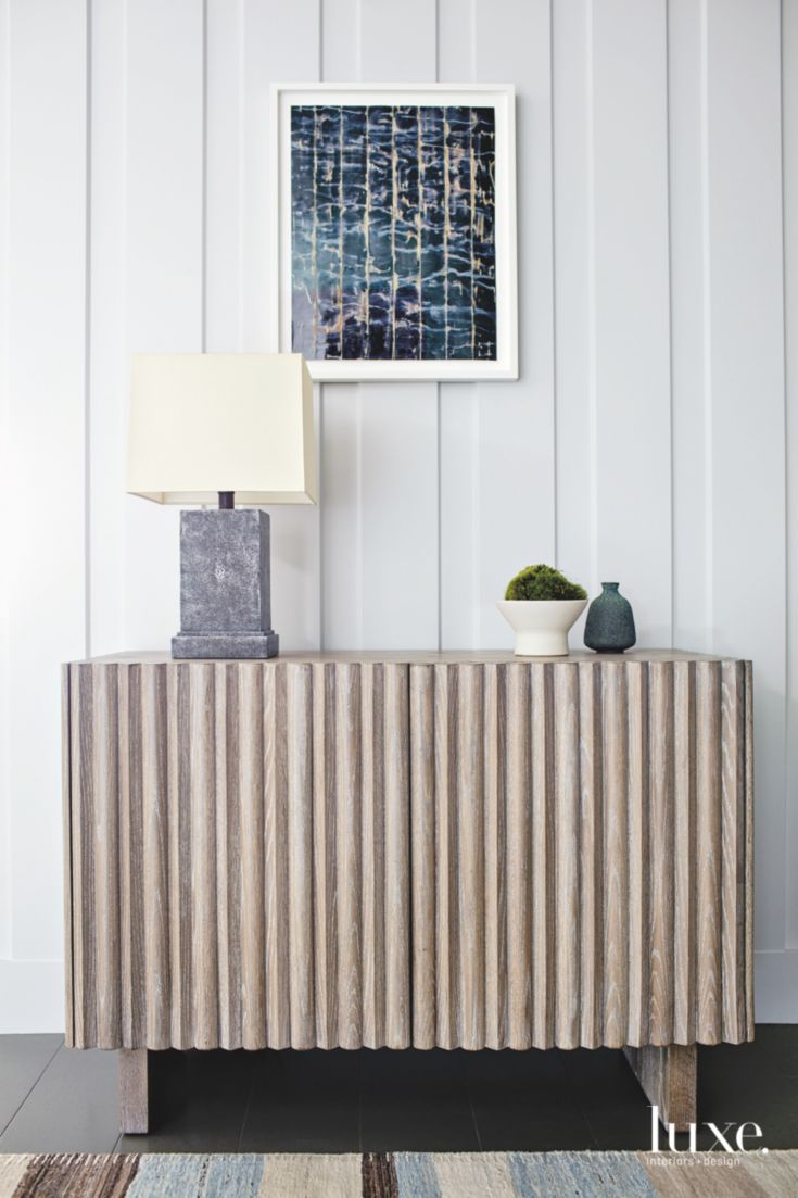 An entry vignette features a bleached-wood Ins & Outs cabinet with a midcentury modern aesthetic, by De Bastiani.