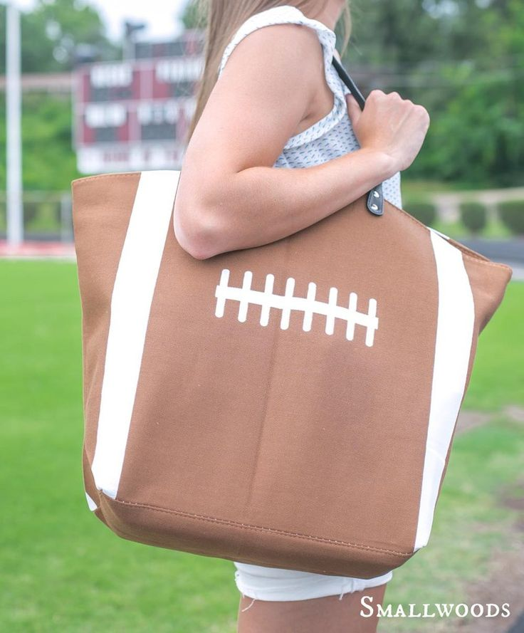 """Our football tote bag is approximately 22""""W x 8""""D x 17""""H. Fully lined with zippered pocket inside. The current ship time for this item is 10-15 business days."""