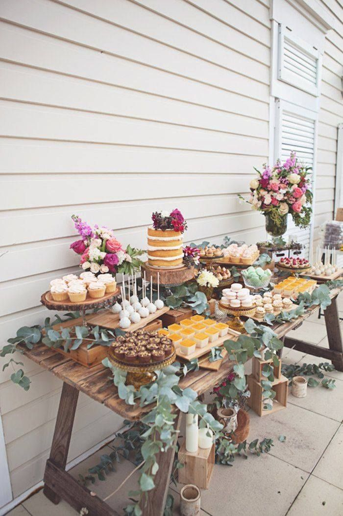 Cake table with variety of desserts, natural look, flowers.