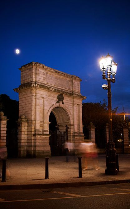 A photograph by photographer Niall O Cleirigh of the traitors arch at St Stephen's green in Dublin Ireland with moon and dusk deep blue sky www.essentia.ie