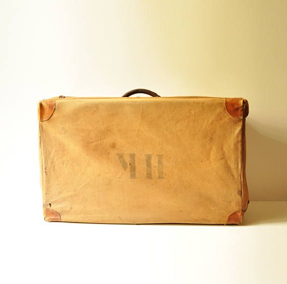 Such a great piece of vintage luggage! A gorgeous genuine brown leather suitcase from the 1940s, with a protective canvas cover, cotton fabric lining and brown leather handle.  The canvas has the initials HK on the outside. It has leather corners. It shows expected wear, a few tears and stains here and there. The leather chocolate brown suitcase is really amazing, quite large, with all metal clasps working well. It does show stains on its outer part. The paper lined inside is overall clean…
