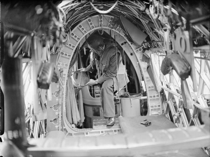 A crew member on board a Vickers Wellington of No. 75 (New Zealand) Squadron RAF places night flares in position in the cramped rear fuselage. Note the Elsan chemical lavatory to the right.