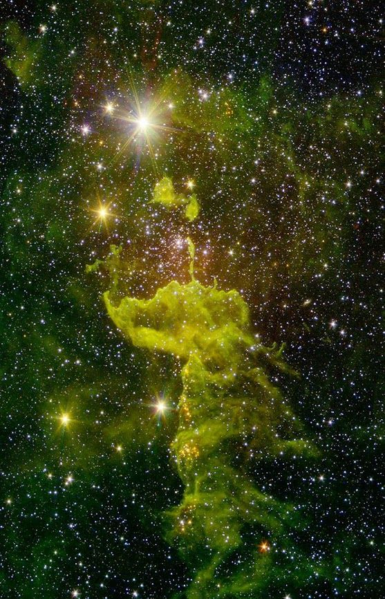 "A nebula known as ""the Spider"" glows fluorescent green in an infrared image from NASA's Spitzer Space Telescope 