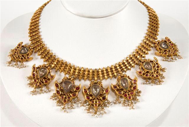 A necklace with 5 gold pendants.  A necklace consisting of 5 gold pendants, set with rubies diamonds, emeralds, suspended are pearls and green glass beads The reverse of each pendant depicts godesses in relief