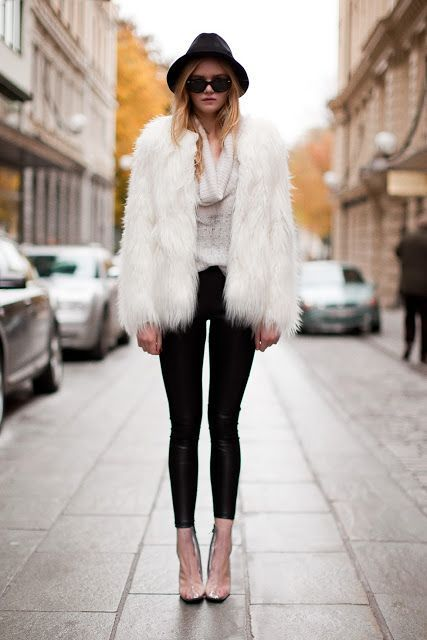Shop this look on Lookastic: http://lookastic.com/women/looks/hat-sunglasses-leggings-fur-coat-cowl-neck-sweater/5432 — Black Hat — Black Sunglasses — Black Leather Leggings — White Fur Coat — Beige Cowl-neck Sweater